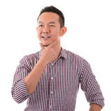 Asian man having a thought. Portrait of casual Asian man having a thought, isolated on white background. Asian male model Stock Image