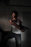 Asian Man hiding in Staircase carrying a gun Stock Photos