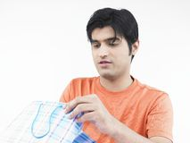 Asian man with his shopping bag. Asian male of indian origin looking through his shopping bag Royalty Free Stock Image