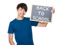 Asian man hold with blackboard and showing phrases of back to sc. Hool isolated on white background Royalty Free Stock Photo