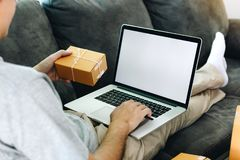 Asian man hold a delivery box for shipping and are using a laptop blank screen.  stock photo