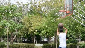 Asian man holding basketball in hand and jumping Throw a basketball hoop Background tree in park. Asian man holding basketball in hand and jumping Throw a stock video footage