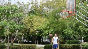 Asian man holding basketball in hand and jumping Throw a basketball hoop Background tree in park. Asian man holding basketball in hand and jumping Throw a stock footage