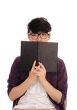 Asian man holding book for face. A young Asian man standing in a checkered shirt and glasses, holding a book in front of his face, isolated for white background Royalty Free Stock Photos