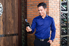 Asian man holding bottle of wine Royalty Free Stock Photo