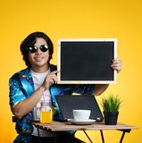 Asian Man Holding Empty Blackboard While Working on Summer Vacat. Ion Season Against Yellow Background Stock Images