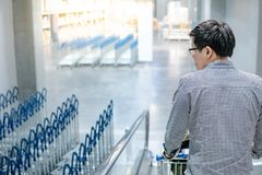 Asian man holding shopping cart on travelator. Young Asian man shopper holding shopping cart trolley on travelator escalator in supermarket or grocery store Stock Photography
