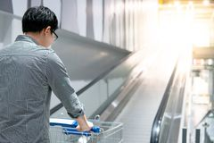 Asian man holding shopping cart on travelator. Young Asian man shopper holding shopping cart trolley on travelator escalator in supermarket or grocery store Royalty Free Stock Images