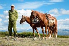 Asian man holding two horses Stock Photo