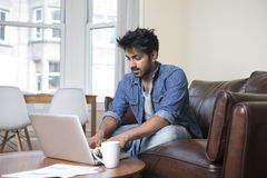 Asian man at home using a laptop. Stock Images
