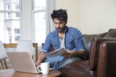 Asian man at home using a laptop. Royalty Free Stock Images