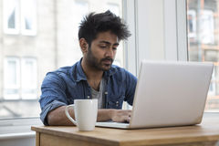 Asian man at home working on laptop. Royalty Free Stock Photo