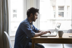 Asian man at home working on laptop. Stock Photo