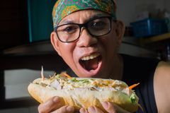 Asian man hungry Baguettes sandwich Stock Photography