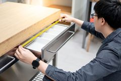 Asian man using tape measure on drawer. Asian man interior designer using tape measure for measuring size of stainless steel drawer on modern counter in kitchen royalty free stock photos