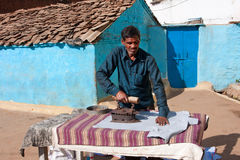Asian man ironing clothes vintage iron. In Orchha, India. 11.2% Uttar Pradesh people work in the secondary sector of the economy (manufacturing Royalty Free Stock Images