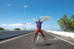 Asian Man jump on the empty highway Stock Photo