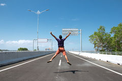 Asian Man jump on the empty highway Royalty Free Stock Photography