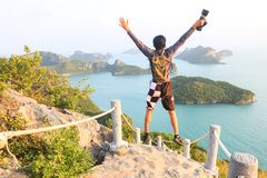 Asian man jumping and enjoying on the top of the mountain royalty free stock photography