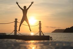 Asian man jumping on floating pier at sunrise , Silhouette body of asian people early morning on the beach by the sea. Asian man standing and jumping on floating stock photos
