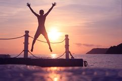 Asian man jumping on floating pier at sunrise , Silhouette body of asian people early morning on the beach by the sea. Asian man standing and jumping on floating royalty free stock images