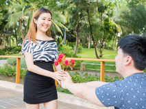 Asian man kneels down giving his girlfriend a bunch of roses Royalty Free Stock Photography
