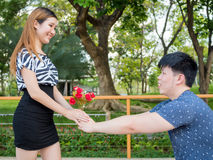 Asian man kneels down giving his girlfriend a bunch of roses Stock Images