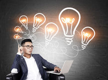 Asian man with laptop and chain of light bulbs Stock Photos