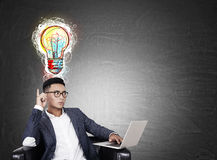 Asian man with laptop and colorful light bulb Royalty Free Stock Image