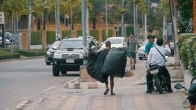 Asian man with large trash bags walks along the sidewalk in slow motion. Thailand. Pattaya. PATTAYA, THAILAND, DECEMBER 16, 2017: Asian man with large trash bags stock footage