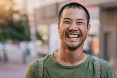 Asian man laughing while standing on a city street. Close up portrait of a casually dressed handsome young Asian man smiling and laughing while standing alone Stock Images