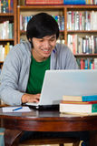 Asian man in library with laptop. Student - Young Asian man in library with laptop and a pile of books learns Royalty Free Stock Images
