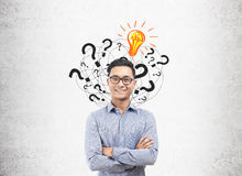 Asian man, light bulb and question marks Stock Images