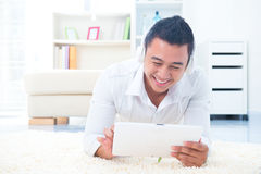 Asian man listen mp3 with headphone. Lying on floor at home Stock Image