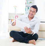 Asian man listen song with headphone. Sitting on floor at home Royalty Free Stock Photos