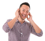 Asian man listening to mp3. Attractive Asian man listening to mp3, isolated on white background, Asian male model Stock Images