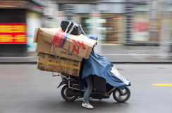Asian man loaded with boxes riding a motorbike Royalty Free Stock Photos