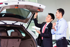 Asian man looking at car in dealership Royalty Free Stock Images