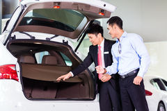 Asian man looking at car in dealership Stock Image