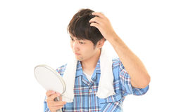 Asian man looking at his face in mirror Stock Image