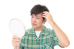 Man looking unhappy with his hair. Asian man looking at his hair in mirror Royalty Free Stock Photo