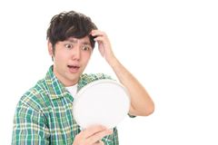 Man looking unhappy with his hair. Asian man looking at his hair in mirror Royalty Free Stock Image