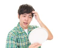 Man looking unhappy with his hair. Asian man looking at his hair in mirror Royalty Free Stock Photography