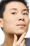 Asian man looking his unshaved chin Stock Image