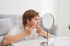 Asian man looking at mirror and popping a pimple.  royalty free stock photo