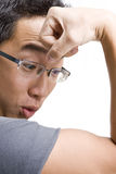 Asian man looking at own bicep Royalty Free Stock Image