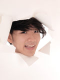 Asian man looking trough hole in paper. Stock Image