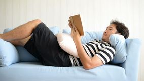 Asian man lying on blue sofa and reading book.  stock video