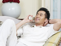 Asian man. Lying on couch talking on phone Royalty Free Stock Image