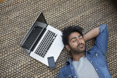 Asian man lying on the floor at home sleeping next to laptop Royalty Free Stock Image